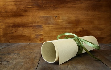 Stock Photo - Close up image of education diploma over wooden table. selective focus