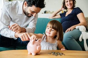 girls puts money into pig