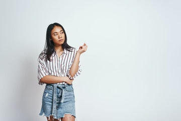 Stock Photo - Cute asian young woman in casual wear is thinking what to do and looking away while standing against grey background